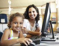 Elementary School Pupil With Teacher In Computer Class Stock Photo