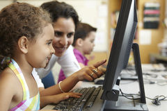 Elementary School Pupil With Teacher In Computer Class Royalty Free Stock Photos