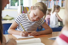 Elementary School Pupil Working At Desk In Classroom Stock Photo