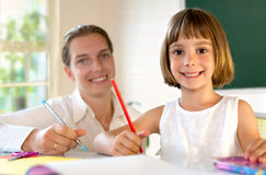 Elementary school pupil working with educator Royalty Free Stock Image