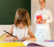 Elementary school pupil working with educator Stock Photography