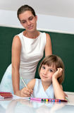 Elementary school pupil working with a teacher Stock Photography