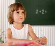 Elementary school pupil writing in a classroom Royalty Free Stock Images