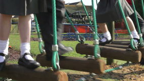 Elementary School Pupils Balancing On Climbing Equipment. Camera pans up from children's feet balancing on climbing equipment to happy expressions. Shot on Canon stock footage