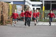 Elementary School Pupils Running In Playground Stock Photos