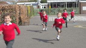 Elementary School Pupils Running Into Playground. Group of schoolchildren open gate to school playground and run towards camera.Shot on Canon 5d Mk2 with a frame stock footage