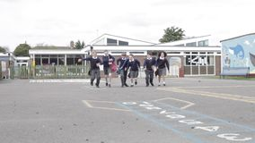 Elementary School Pupils Running Towards Camera. Group of pupils run across playground towards camera. Shot on Canon 5d Mk2 with a frame rate of 30fps stock video