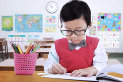 Elementary school student drawing on the paper Stock Image