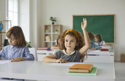 Elementary school student raises her hand, ready to answer the teacher's questions in class.