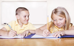 Elementary School Students doing Homework. Two elementary school kids in a classroom goofing around and playing while trying to do school work Royalty Free Stock Photography
