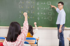 Elementary school students raising hands. In the classroom Royalty Free Stock Image