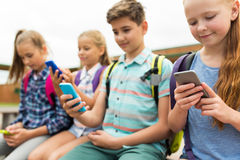 Elementary school students with smartphones Stock Images