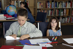 Elementary school students studying. Two Elementary school students studying in library. One is making paper airplane and the other is bored Stock Photos