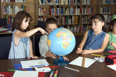 Elementary school students studying. In library stock photography