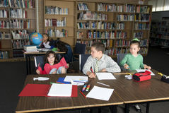 Elementary school students studying. Elementary school students study in library. Some are bored others work stock photography