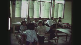 Elementary school teacher and children. Thailand, Mae Salong, December 1983. Three shot sequence inside of an elementary school classroom, with many children stock video footage