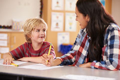 Elementary school teacher in class at desk with schoolboy Stock Image