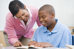 Elementary school teacher helping pupil Stock Photography