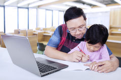 Elementary school teacher helps his student. Portrait of male elementary school teacher teach his female student to write on the book Royalty Free Stock Photo