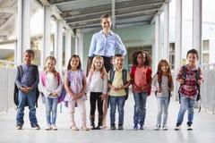 Elementary school teacher and her pupils in school corridor stock photography