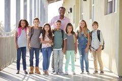 Elementary school teacher and his pupils in school corridor stock photos