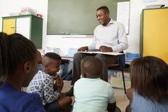 Elementary school teacher reading to kids sitting on floor Stock Photo