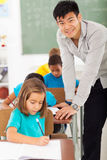 Elementary school teacher. Smiling elementary school male teacher in classroom with students Stock Images