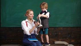 Elementary school teacher and student in classroom. Back to school. Elementary school. Lesson Individual School Biology stock footage