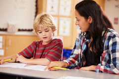 Elementary school teacher working at desk with schoolboy Stock Image