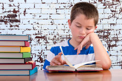 Elementary schoolboy focusing on his studies. Elementary schoolboy is focusing on his studies sitting at a desk in the classroom with a stack of colored Stock Image