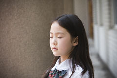 Elementary schoolgirl praying Stock Images