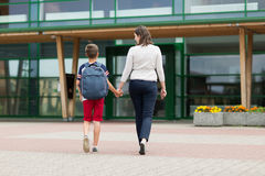 Elementary student boy with mother going to school Royalty Free Stock Photo