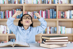 Elementary student celebrating her success in library. Portrait of elementary student celebrating her success while sitting with books on desk in the library stock photo