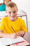 Elementary student classroom. Adorable elementary student in classroom writing classwork royalty free stock photography