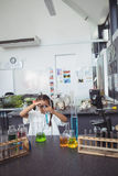 Elementary student doing experiment with blue chemical at laboratory Royalty Free Stock Images
