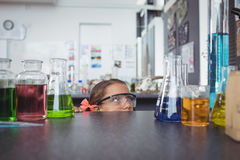 Elementary student hiding behind desk in laboratory Stock Photography