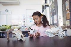 Elementary student holding animal skull by desk Stock Photo