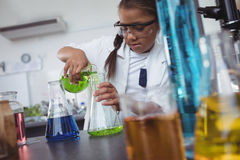 Elementary student pouring green chemical in flask at laboratory Stock Photo