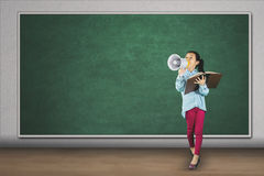 Elementary student shouting with megaphone. Full length of elementary student shouting with megaphone while holding a book in front of blank chalkboard Royalty Free Stock Image
