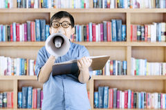 Elementary student shouting on megaphone in library Stock Image