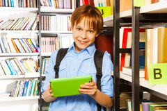 Elementary student with tablet in library Royalty Free Stock Image