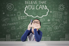 Elementary student with text of motivation. Male elementary school student pointing and looking at a text of Believe That You Can on the chalkboard Royalty Free Stock Image