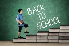 Elementary student walking on books stair Stock Photos