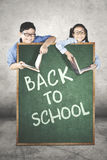 Elementary students behind a chalkboard Royalty Free Stock Photos