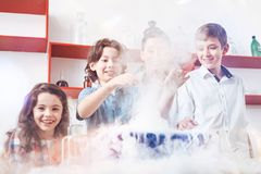 Elementary students conducting experiment in science classroom. Hiding in the fog. Group of extremely excited little scientists using a chemistry set during a Stock Images