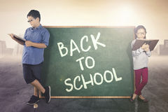 Elementary students lean with a chalkboard Stock Photos