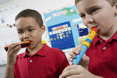 Elementary Students in Music Class. Elementary school boys playing musical instrument in class Stock Image
