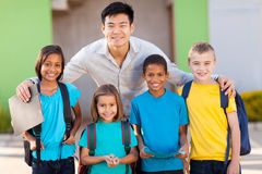 Elementary students teacher. Four elementary school students and teacher on campus royalty free stock photos