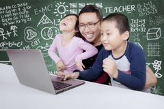 Elementary students using a laptop with their teacher Stock Images