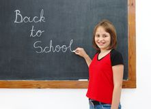 Elementary writing Back to School on chalkboard. Elementary school girl writing Back to School on chalkboard Royalty Free Stock Images